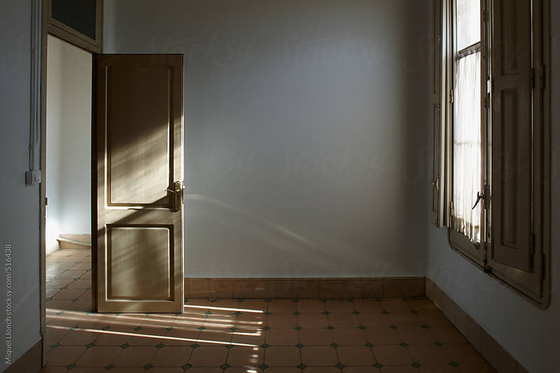 Interior of an old empty room with a window by Miquel Llonch for Stocksy United