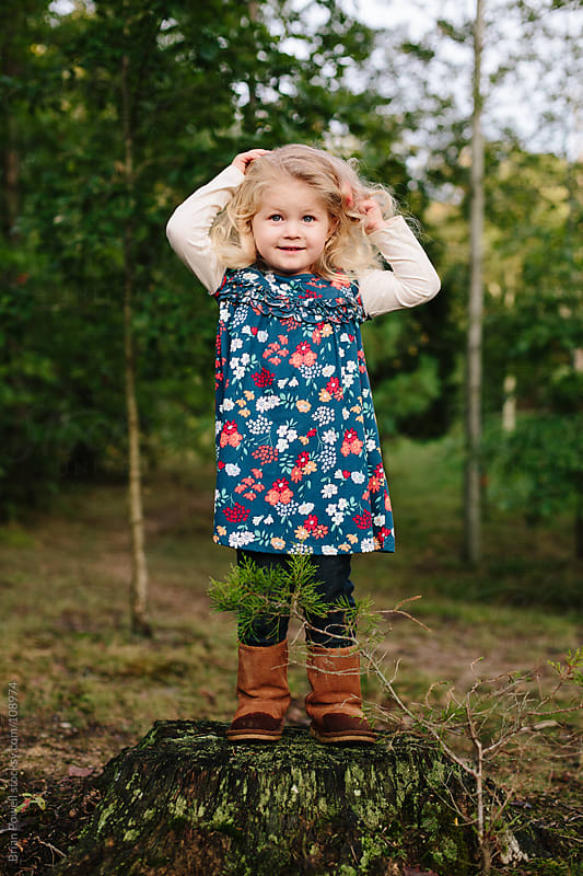 little girl standing on a stump by Brian Powell for Stocksy United