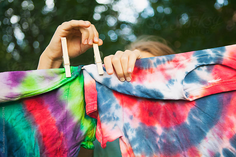 Tie Dye: Girl Puts Shirts Up To Dry by Sean Locke for Stocksy United