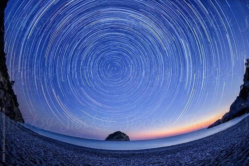 Star trails over the northern sky on a beach. by Helen Sotiriadis for Stocksy United