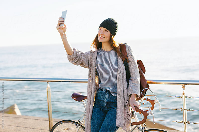 Young woman taking a selfie with her vintage bicycle by the sea. by BONNINSTUDIO for Stocksy United