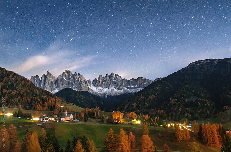 small italian village with the Geisler Mountain group in a starry night by Leander Nardin for Stocksy United