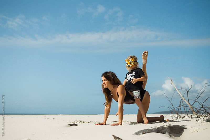 Mother and son wearing a tiger mask playing on an empty beach  by Tahl Rinsky for Stocksy United
