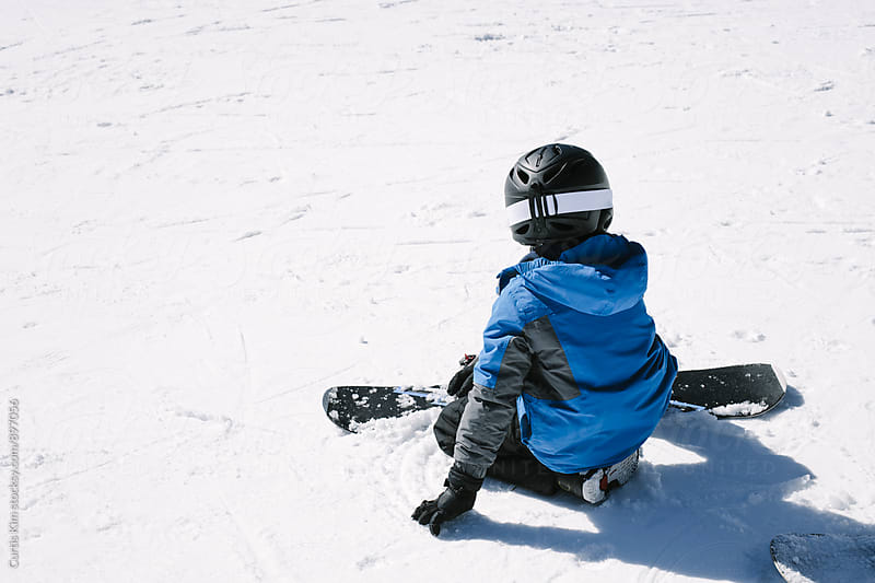 Young boy getting ready to ride his snowboard by Curtis Kim for Stocksy United
