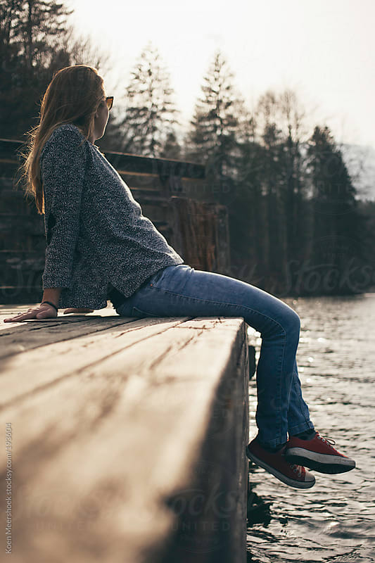 Girl sitting on a jetty at a lake with beautiful mountains in the background. by Koen Meershoek for Stocksy United
