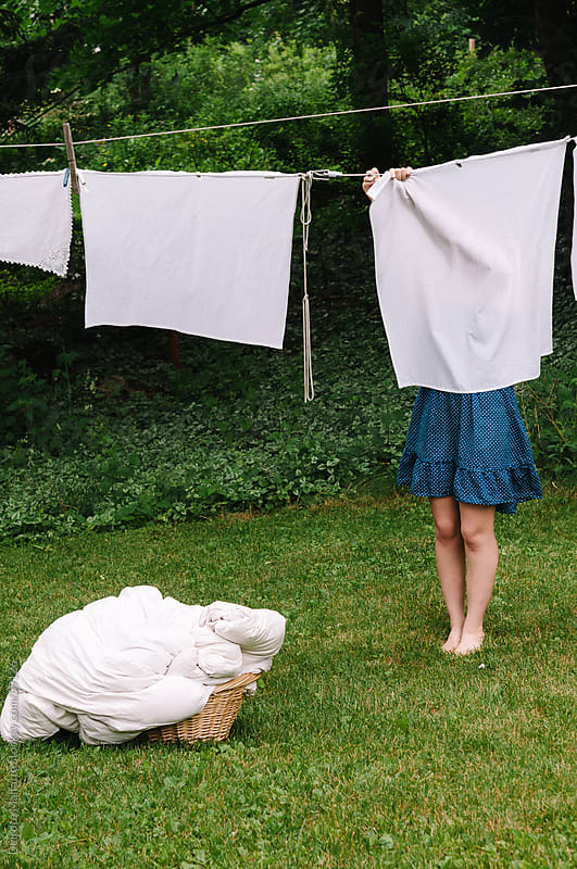 Girl hanging laundry to dry on a clothesline by Deirdre Malfatto for Stocksy United