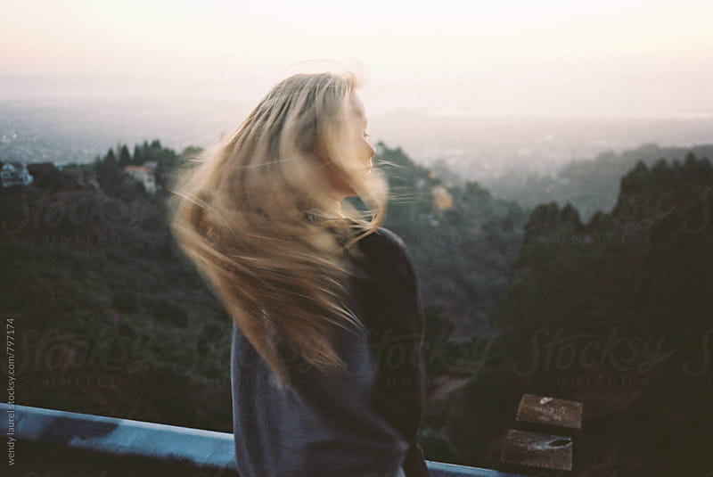 blonde teen at hilltop overlooking bay at sunset moving hair shaking head by wendy laurel for Stocksy United