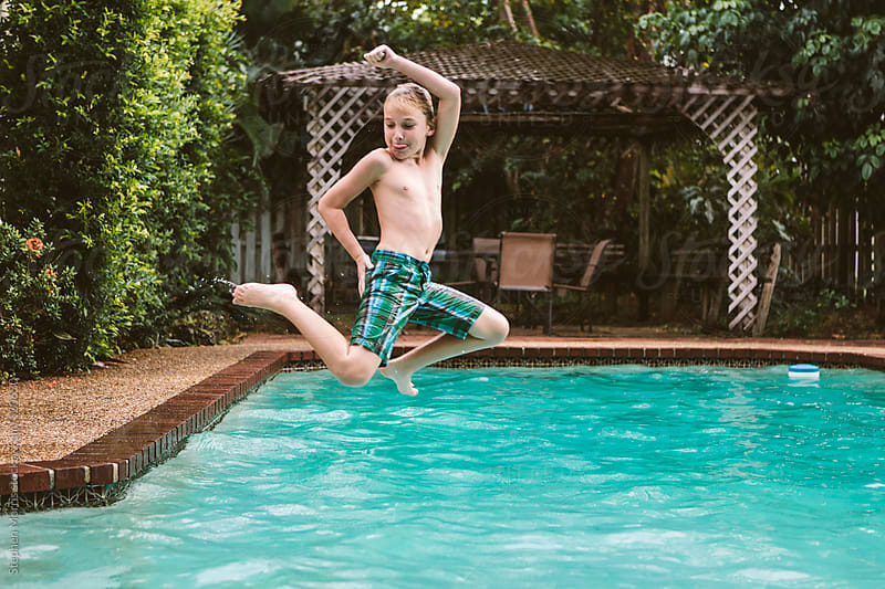 Boy jumping into pool by Stephen Morris for Stocksy United