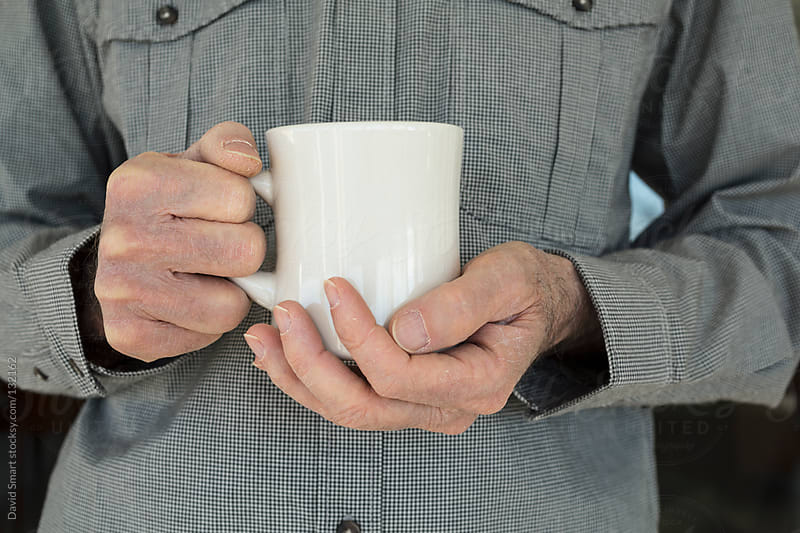 Man holding a white coffee mug with both hands by David Smart for Stocksy United