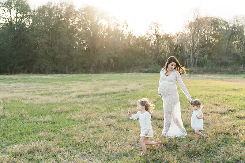 A Mother Walks With Her Young Daughters by Alison Winterroth for Stocksy United