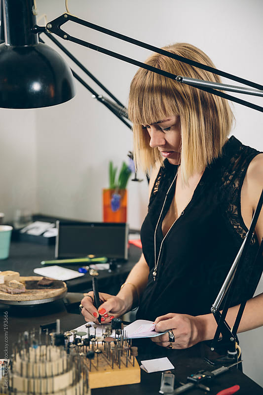 A jewelry designer taking an order in her studio by Lior + Lone for Stocksy United