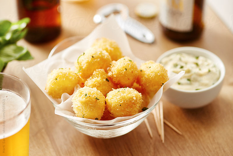 Deep fried mini mozzarella on baking paper in glass bowl by Martí Sans for Stocksy United