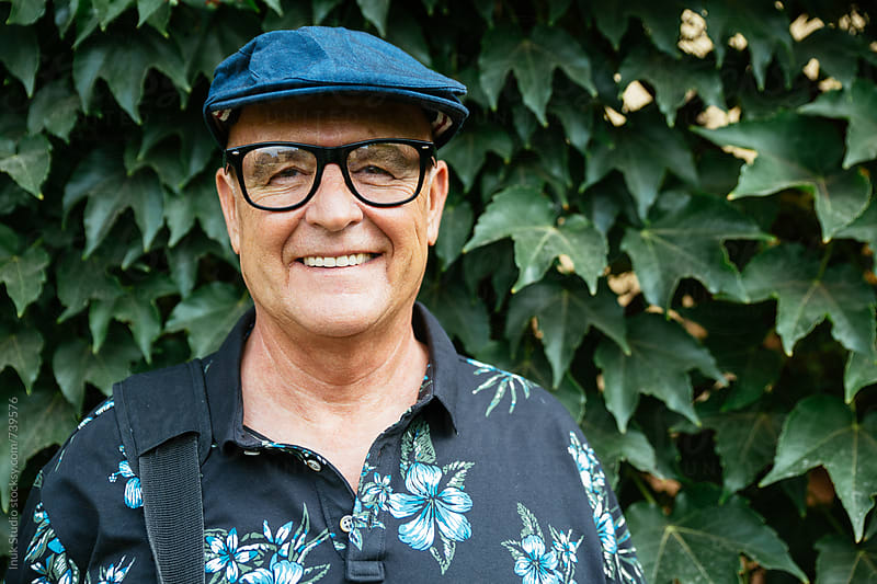 Hipster senior man portrait smiling with a beret and glasses in front of an ivy background by Inuk Studio for Stocksy United