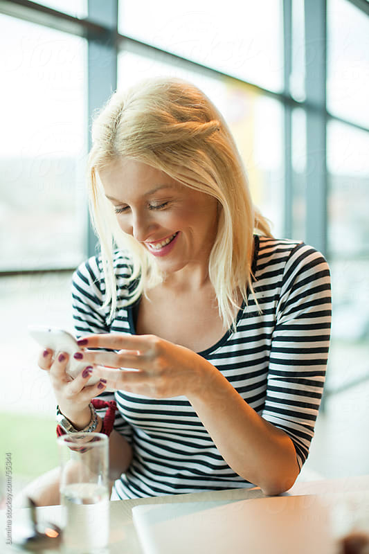 Woman Texting at a Cafe  by Lumina for Stocksy United