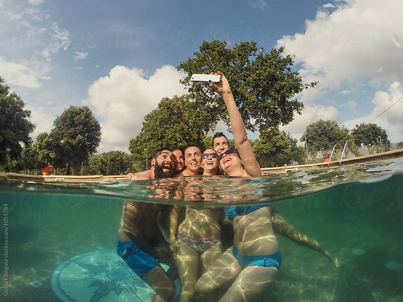 cheerful friends taking selfie using phone in pool by Guille Faingold for Stocksy United