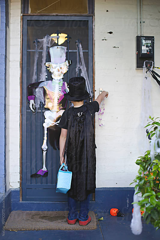 Young boy rings door bell for trick or treat on Halloween by Natalie JEFFCOTT for Stocksy United