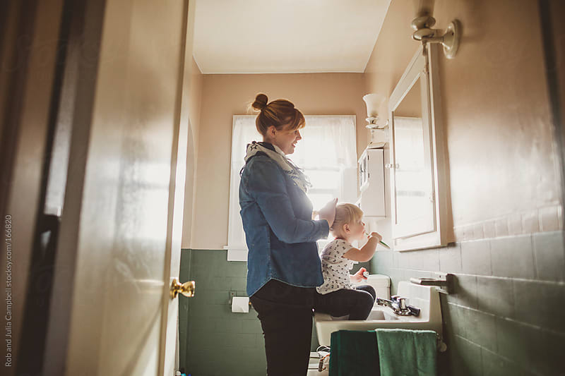 Young mom brushing toddler daughters hair in bathroom  by Rob and Julia Campbell for Stocksy United