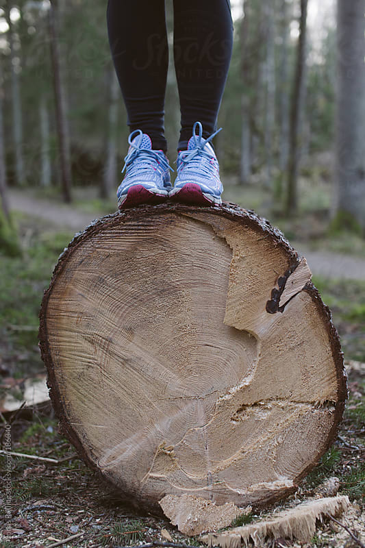 Women in running shoes standing on a fallen tree. by Jonas Räfling for Stocksy United