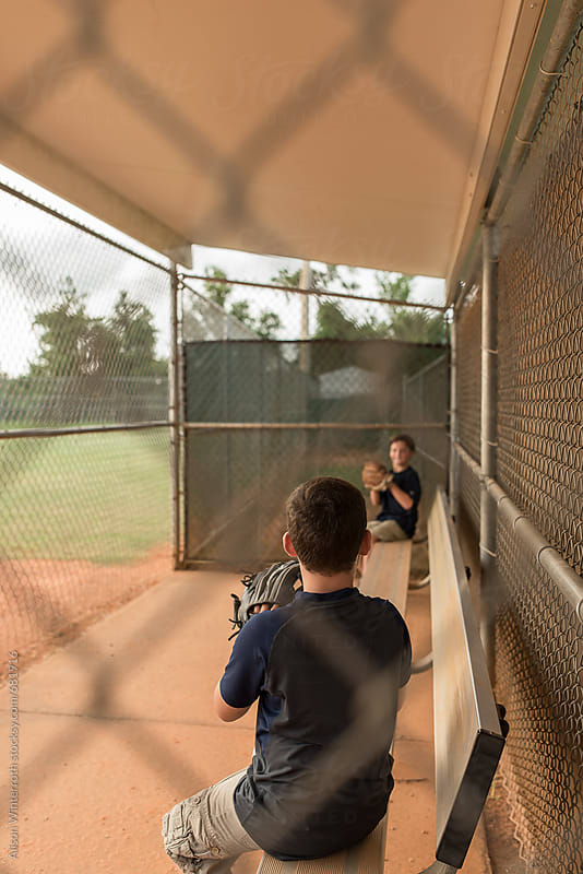 Two Boys Play Catch In A Dugout  by Alison Winterroth for Stocksy United
