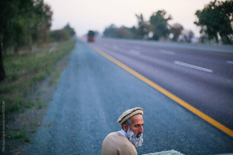 A man praying roadside  by Murtaza Daud for Stocksy United