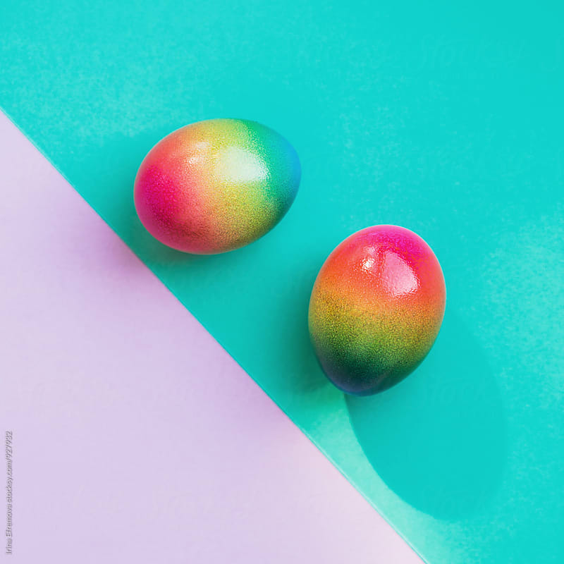 Two rainbow colored eggs on a light purple and turquoise background by Irina Efremova for Stocksy United