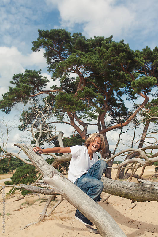 Blonde teenage boy climbing fallen tree branches by Cindy Prins for Stocksy United