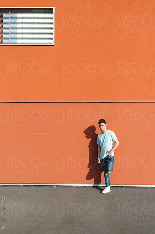 Cool asian man portrait against big orange wall by GIC for Stocksy United