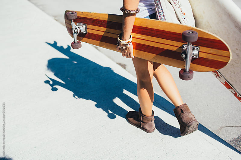 Woman walking with her surfboard and longboard by michela ravasio for Stocksy United