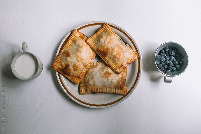 milk, hand pies and blueberries  by Ariana Babcock for Stocksy United