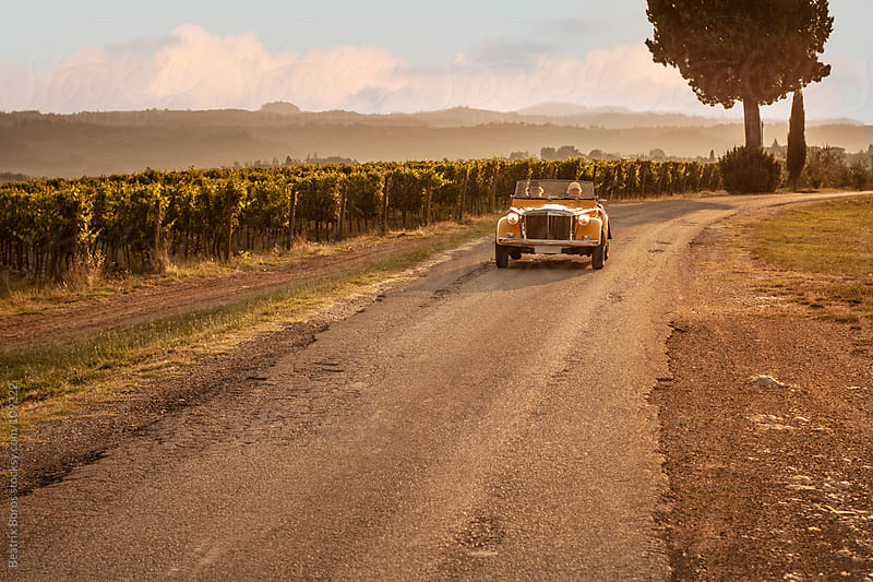Road trip by old fashoned car on Tuscan hills by Beatrix Boros for Stocksy United