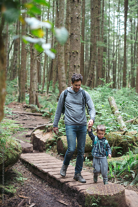 Young caucasian dad spending time with kids outdoors in the woods by Rob and Julia Campbell for Stocksy United