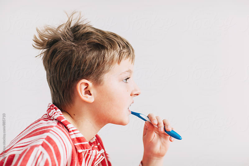 boy with bedhead brushing his teeth in the morning  by Kelly Knox for Stocksy United