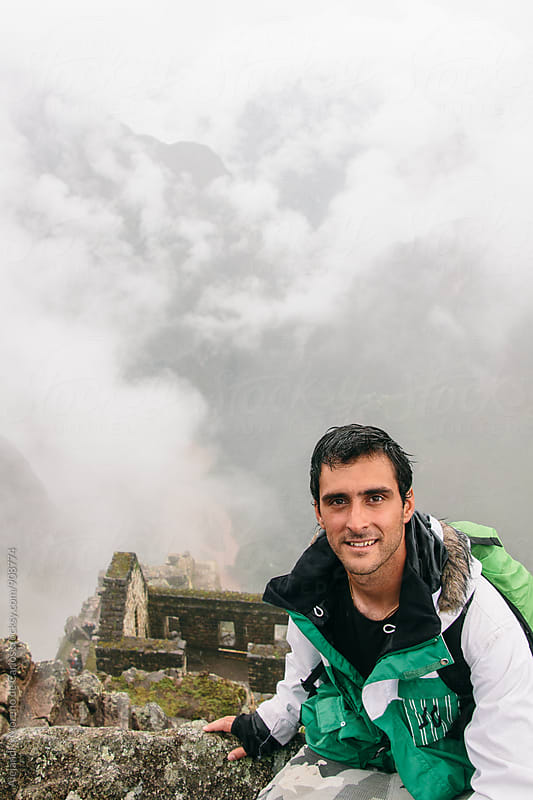Smiling brunet backpacker against of ancient ruined building in mountains by Alejandro Moreno de Carlos for Stocksy United