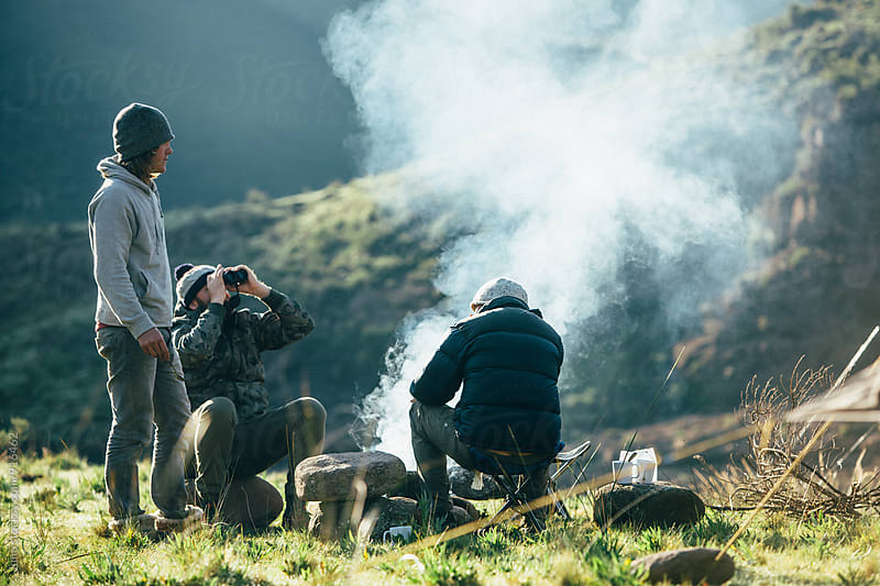Hikers around an early morning camp fire in the mountains by Micky Wiswedel for Stocksy United