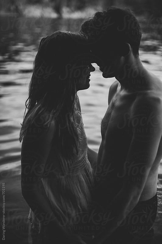 Intimate engaged couple in the lake water at dusk by Daring Wanderer for Stocksy United
