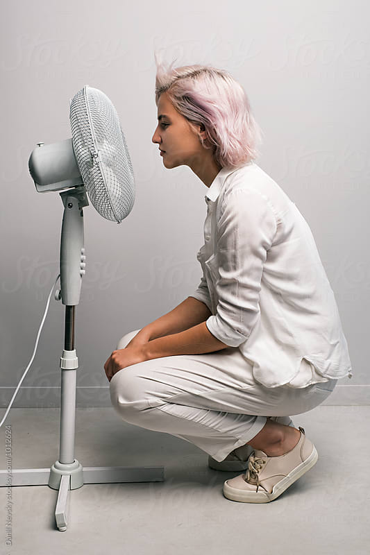 Side view of pink-haired girl against of fan by Danil Nevsky for Stocksy United