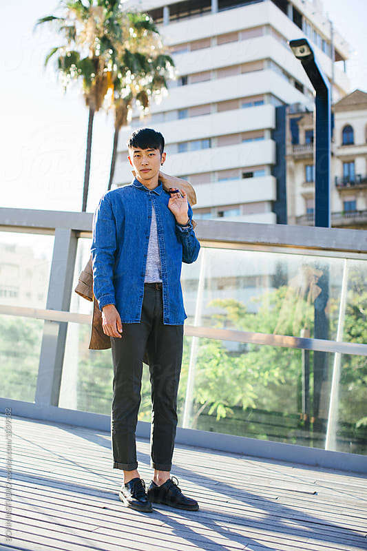 Stylish young asian man in the street. by BONNINSTUDIO for Stocksy United