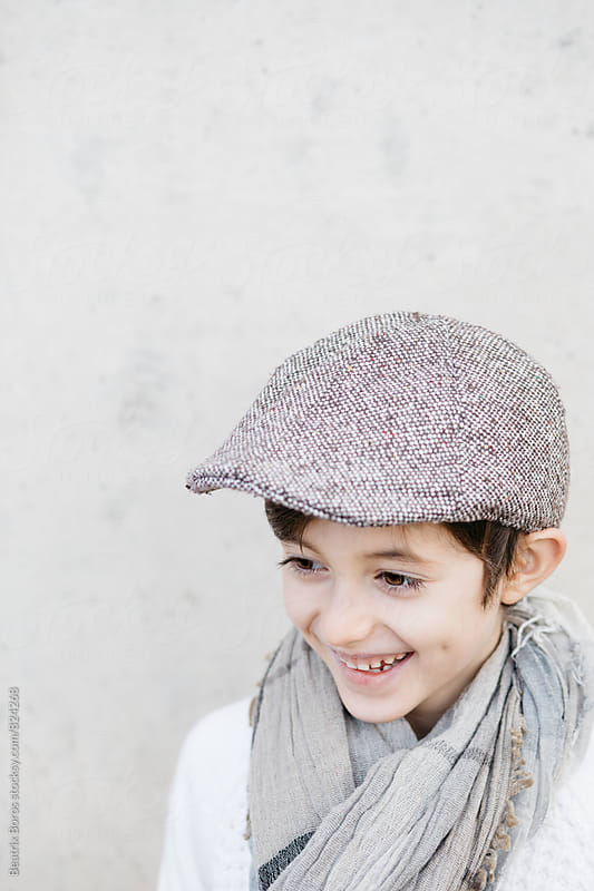Boy looking away laughing  by Beatrix Boros for Stocksy United