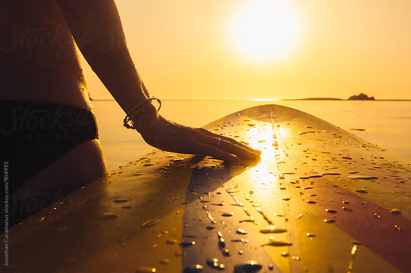 Young woman's hand on surfboard in the ocean with golden light by Jonathan Caramanus for Stocksy United