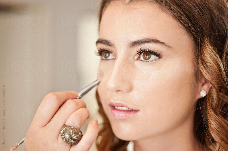 applying make up by Gillian Vann for Stocksy United