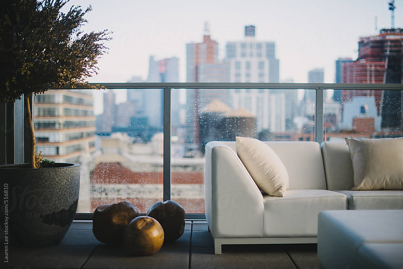 White couch on a roof deck by Lauren Naefe for Stocksy United