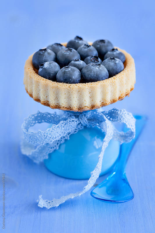 cake with blueberries on a cake stand with spoon and blue background by Corinna Gissemann for Stocksy United