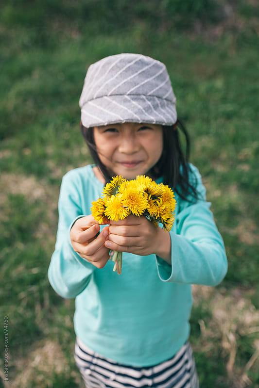 girl holding flower by jira Saki for Stocksy United