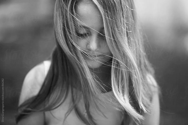 Girl with long blowing hair looking down by Dina Giangregorio for Stocksy United