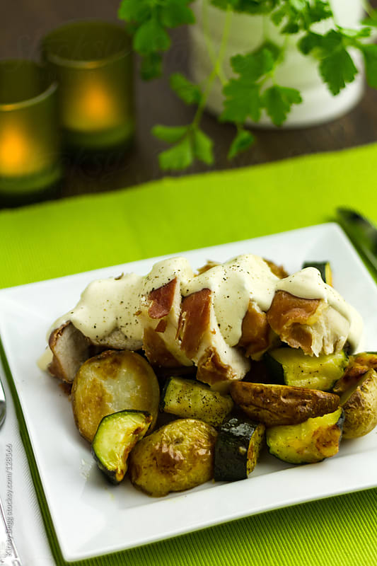 Prosciutto wrapped chicken with courgette and new potatoes by Kirsty Begg for Stocksy United