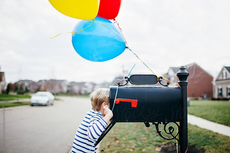 child looking for a birthday surprise inside his mailbox by Kelly Knox for Stocksy United