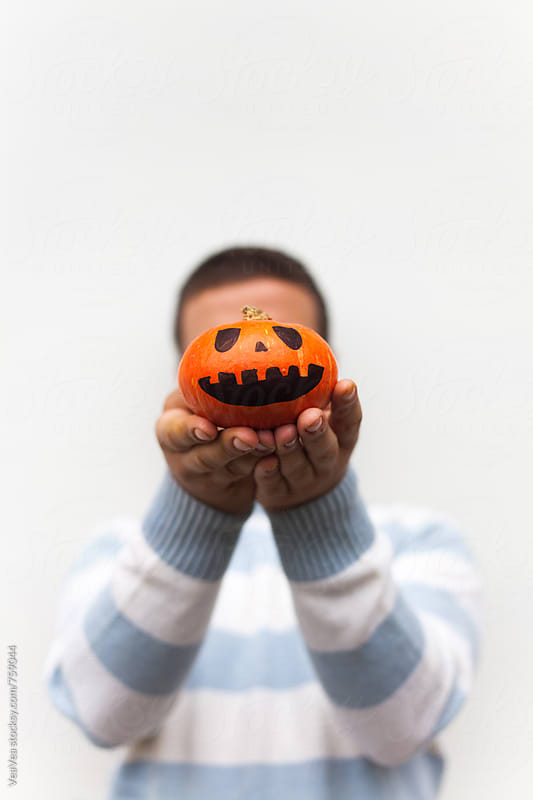 Man holding a small Halloween pumpkin in front of his head  by Marija Mandic for Stocksy United
