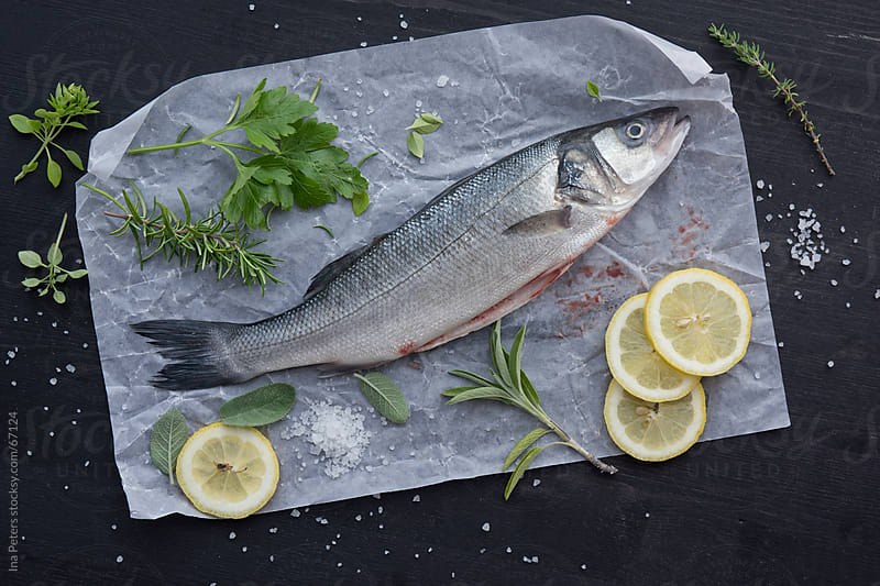 Food: Raw Fish, Loup de mer, sea perch being prepared with herbs by Ina Peters for Stocksy United