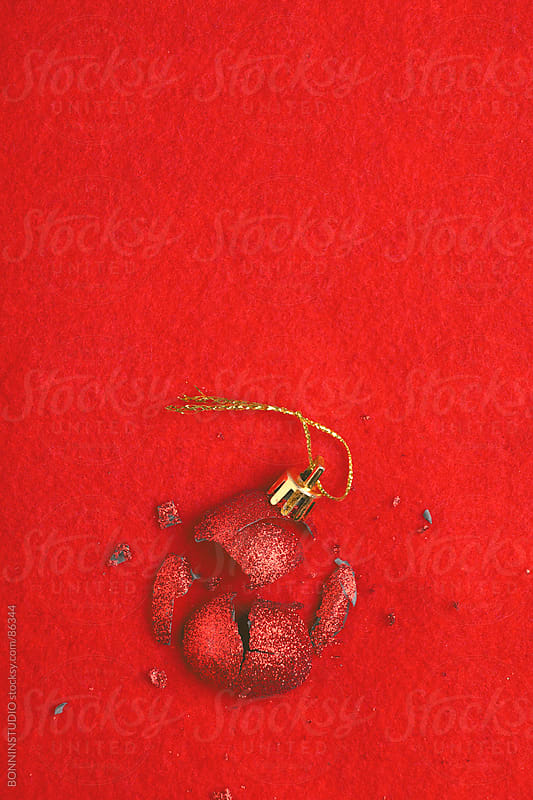 Overhead photo of crushed red christmas ball over red background. by BONNINSTUDIO for Stocksy United