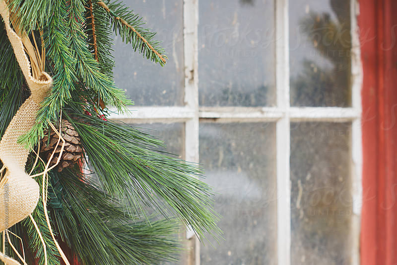 A rustic evergreen decorated with burlap and raffia hangs along an old window by Tana Teel for Stocksy United
